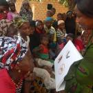 Guinean women looking at a bat safety book at a community outreach event